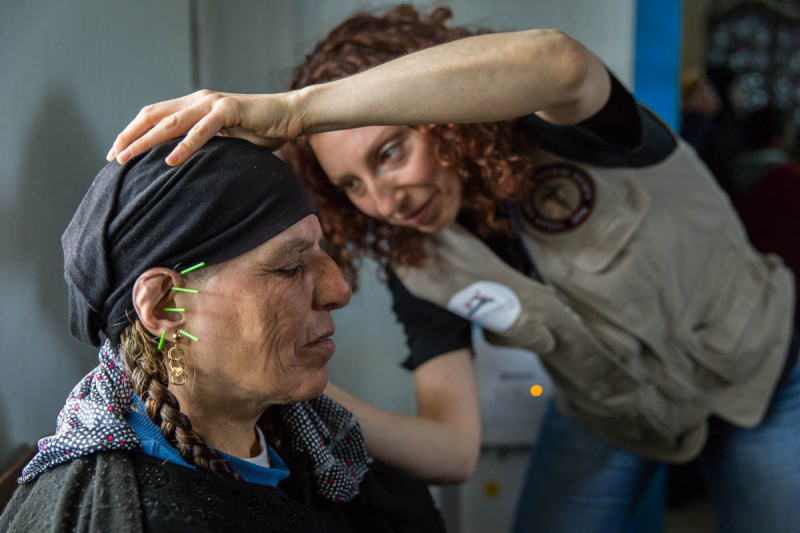 Gabrielle Steinberg, an acupuncturist from Vancouver, treats a Syrian woman at a refugee camp last month. GoDocs offers both Western and Eastern medicine and deploys both naturopaths, like Lustig, as well as homeopaths and acupuncturists. Courtesy Maranie Staab